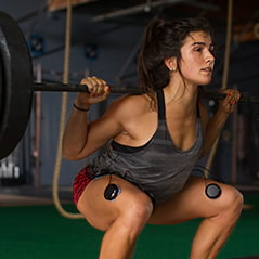 A woman wearing Compex electrodes while lifting weights